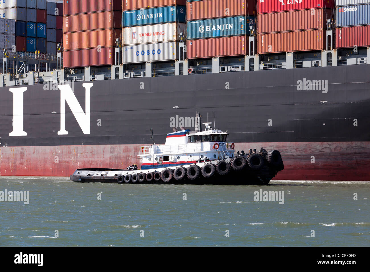 Hanjin shipping container ship, flagged by a tugboat, entering port of Oakland - California USA Stock Photo