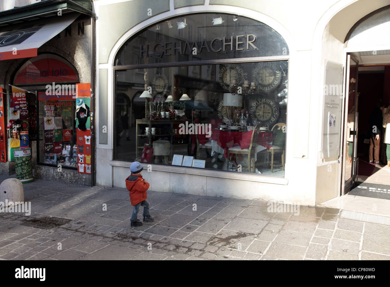CHILD OUTSIDE H. GEHMACHER SHOP SALZBURG AUSTRIA 27 December 2011 - Stock Image