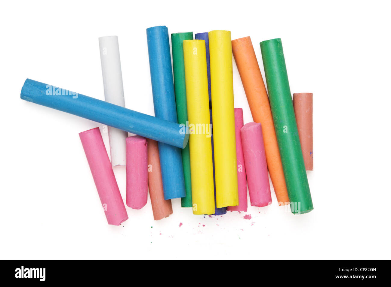 Top down view of group of colored artist pastel chalks isolated on white. Some chalks broken with scattered flakes. - Stock Image