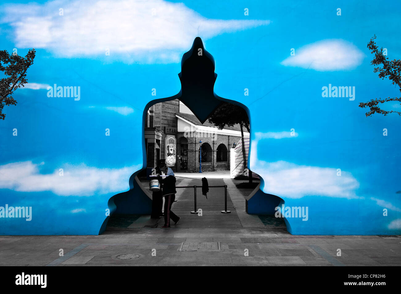 Buddha shaped surrealist door in a blue wall - Zhouzhuang near Shanghai, China - Stock Image