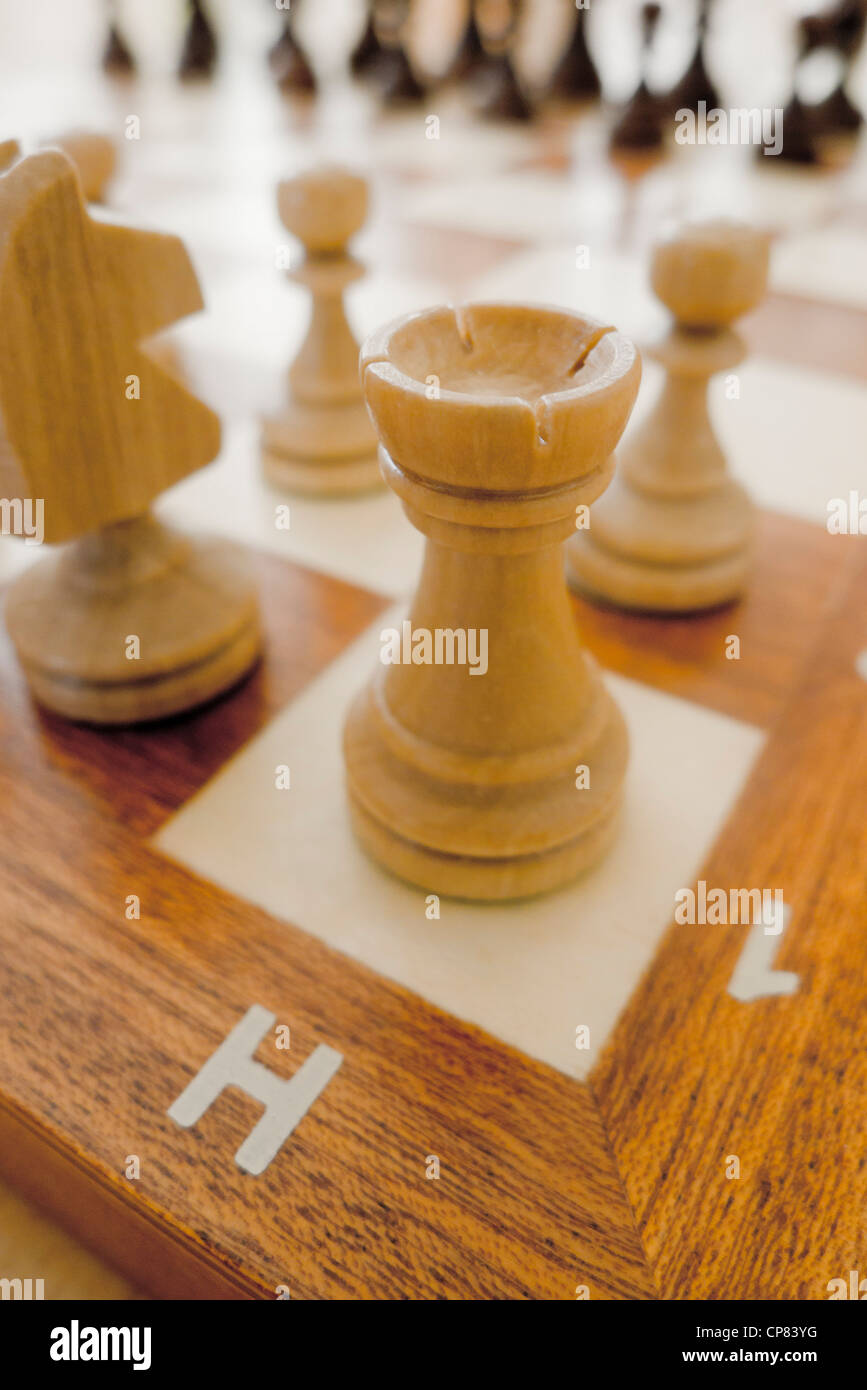chess pieces on the chessboard, rook in the forefront - Stock Image