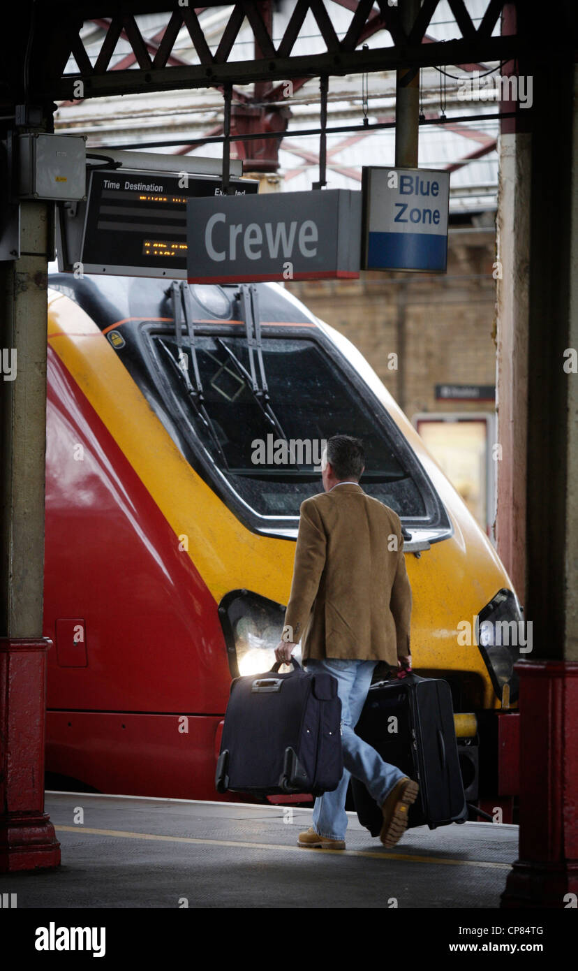 Crewe railway station a passenger walking along the platform past a Virgin Voyager train - Stock Image