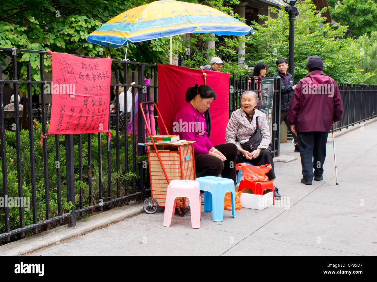 A Chinese fortune teller listens to her client in Chinatown, New York City. - Stock Image