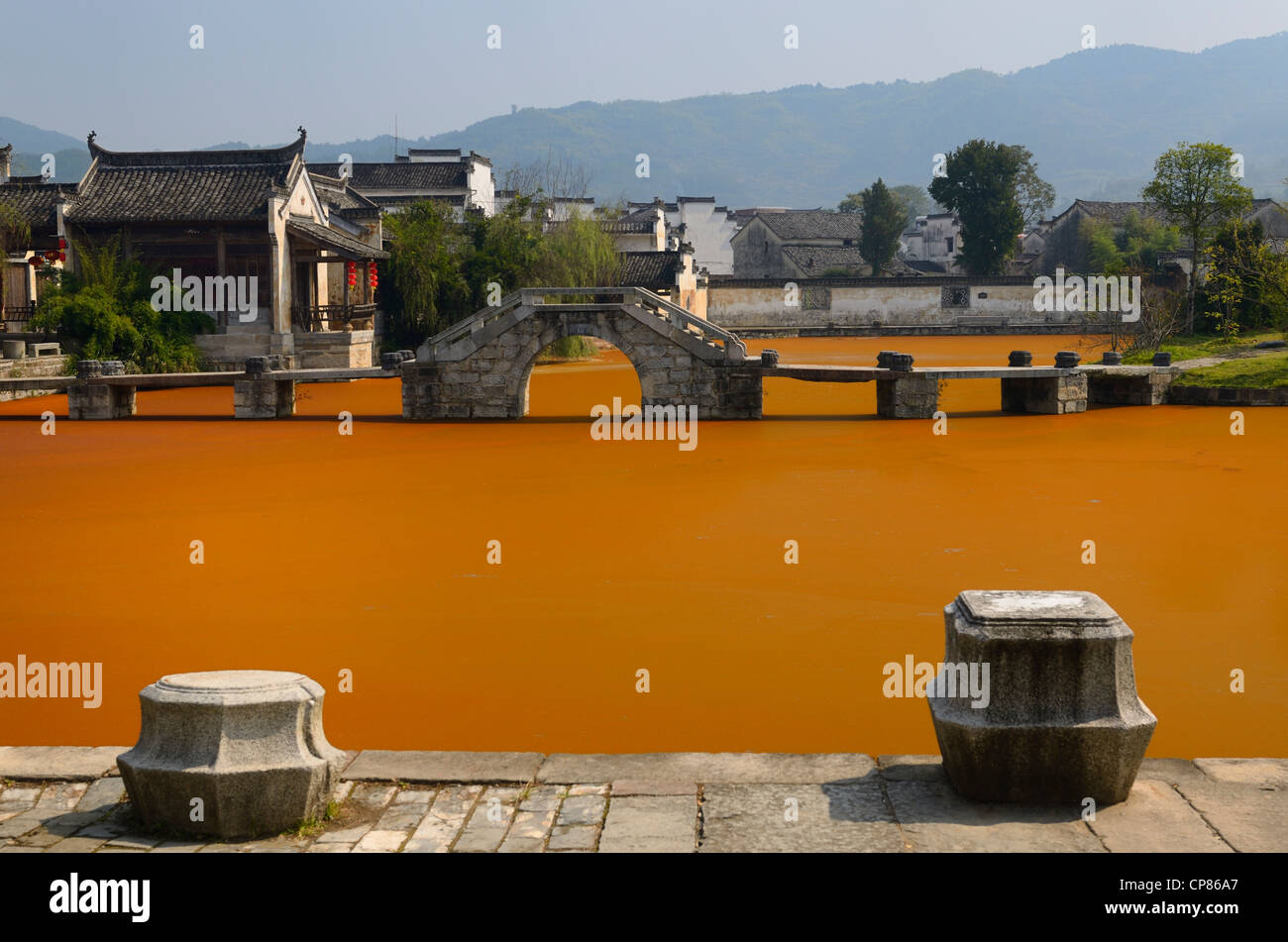 Stone moorings and bridge with bright red algae bloom scum on Longxi river in ancient Chengkan village Huangshan - Stock Image