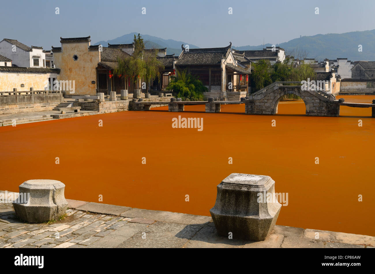 Stone moorings and bridge with bright red algae bloom scum on Longxi river in Chengkan village Huangshan Peoples - Stock Image