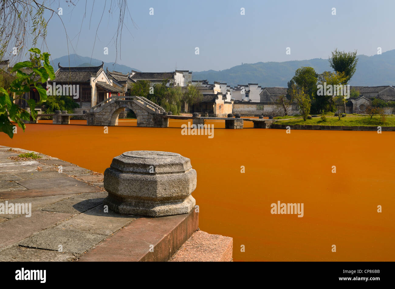 Stone steps and bridge with bright red algae bloom scum on Longxi river in Chengkan village Huangshan Peoples Republic - Stock Image