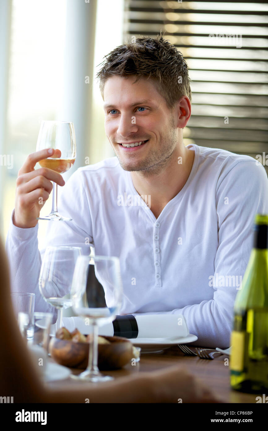 Portrait of a handsome guy holding a glass of wine at a restaurant - Stock Image