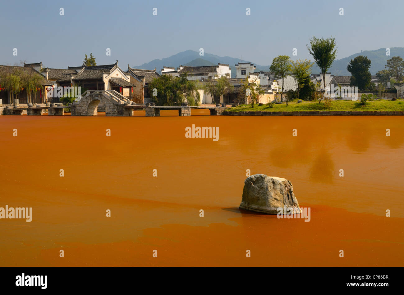 Bright red Euglena algae bloom scum surrounding rock in Longxi river with stone bridge in Chengkan village Huangshan - Stock Image