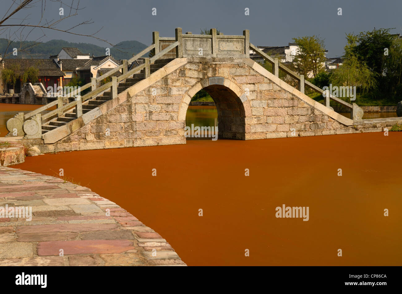 Stone bridge with bright red algae bloom scum on Longxi river in Chengkan village Huangshan Peoples Republic of - Stock Image