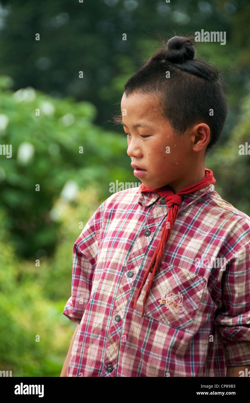 Young Basha Miao (Gun Men) boy with traditional hairstyle and red neckerchief, Southern China - Stock Image