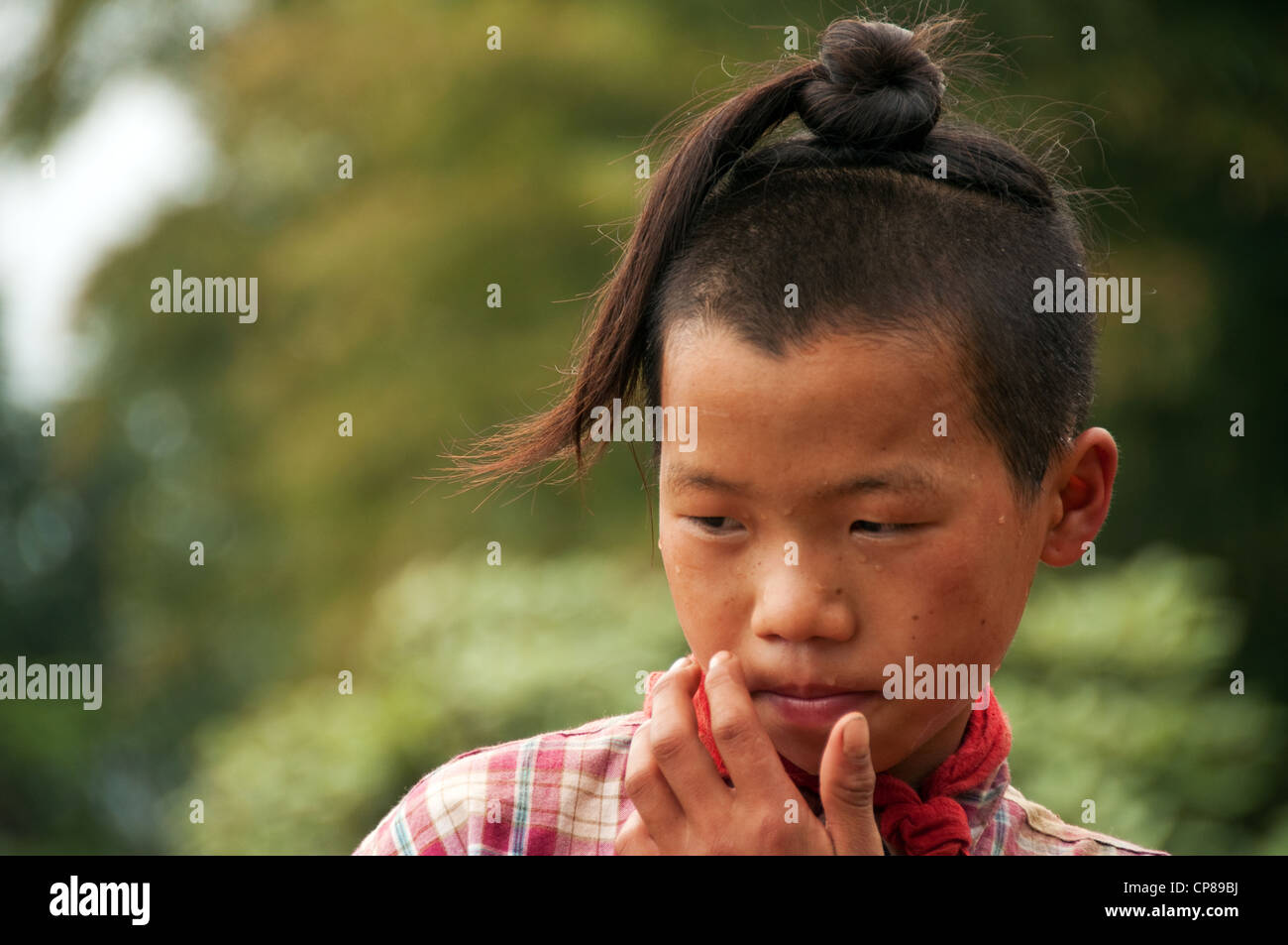 Sweating young Basha Miao (Gun Men) boy with traditional hairstyle and red neckerchief, Southern China - Stock Image