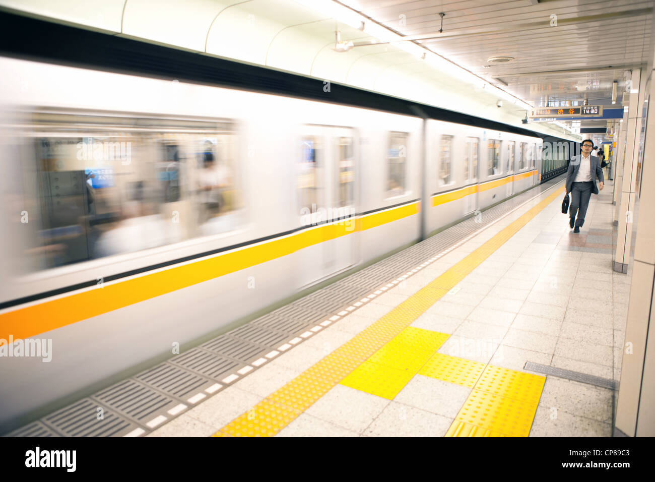 Man walking on platform of a Tokyo subway station, Japan. - Stock Image
