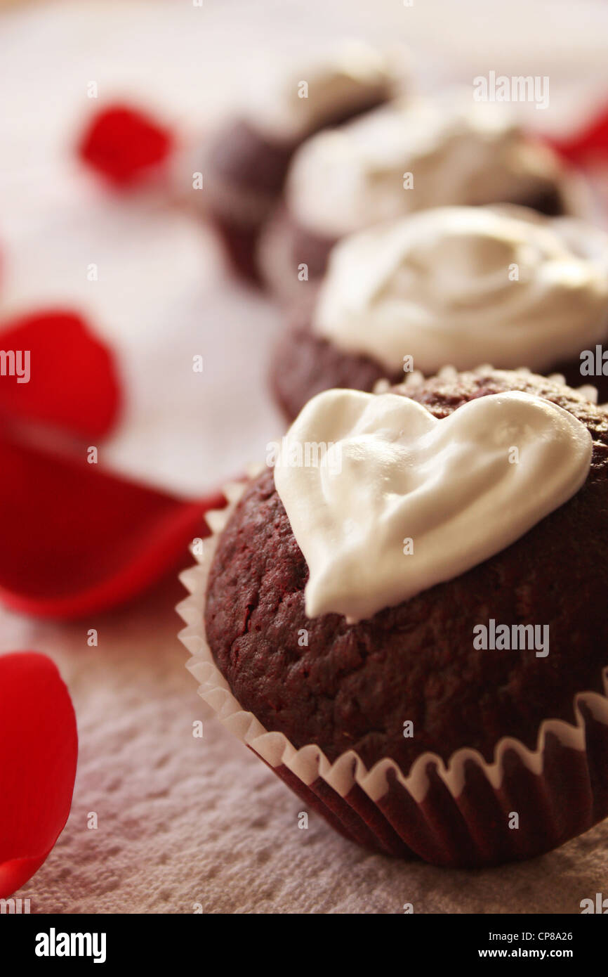 Valentine day themed red velvet cupcakes with heart shaped cream cheese topping. Rose petals are seen in the background - Stock Image