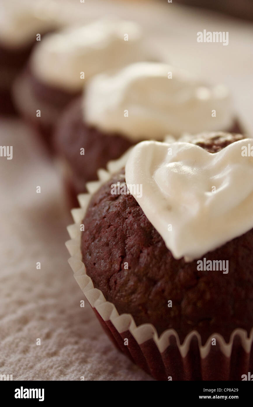 Red Velvet Cupcakes With Heart Shaped Cream Topping Are Lined Up On A Table. Edible Valentine Gifts. - Stock Image