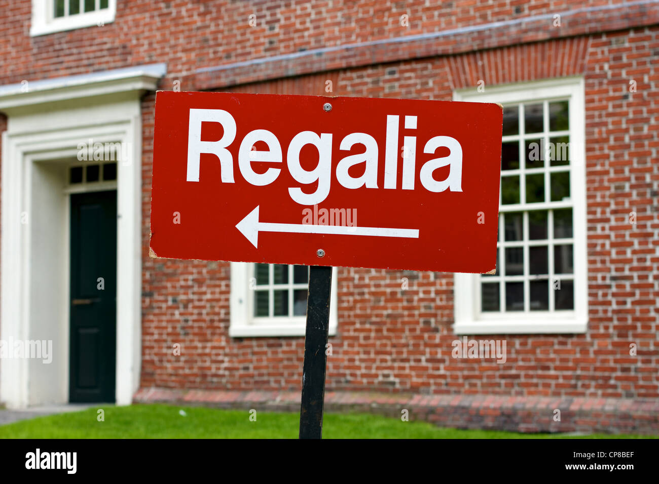 Red sign shows graduates where to pick up their graduation ceremony cap and gown, or regalia, on the eve of Harvard - Stock Image