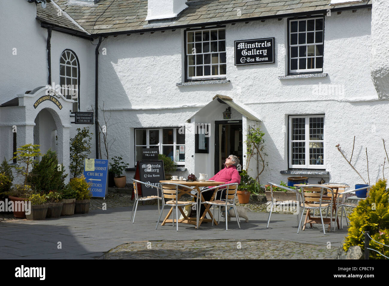 Woman relaxing outside the Minstrels Gallery Tea Room in the village of Hawkshead, Lake District National Park, - Stock Image