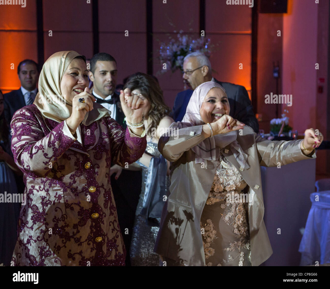 veiled middle-aged relatives of the bride and groom dancing at Egyptian wedding, Cairo, Egypt - Stock Image