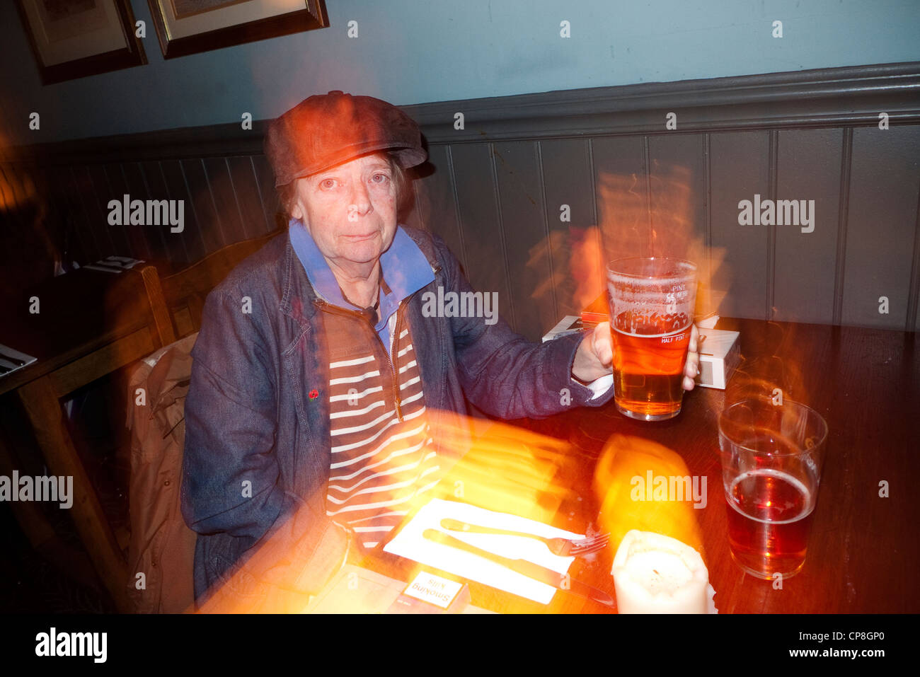 Eccentric looking woman raises a pint of beer in a pub, London, England, UK (slow sync flash) - Stock Image