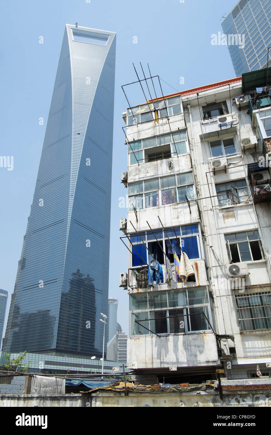 Contrast between old apartment building with modern skyscrapers to rear in Lujiazui financial district in Shanghai Stock Photo