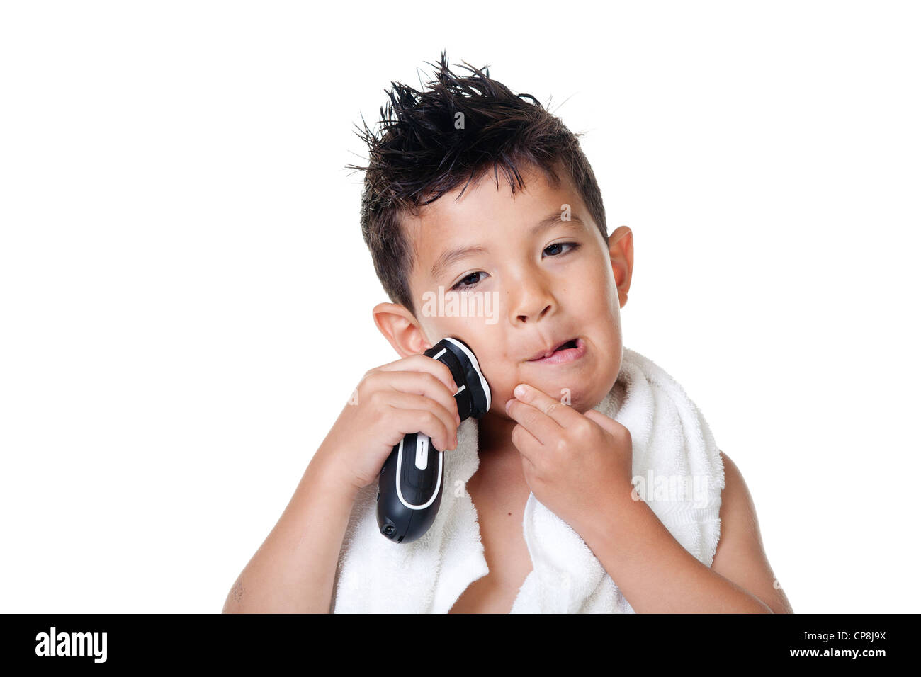 Boy has fun pretending to shave with an electric razor. - Stock Image