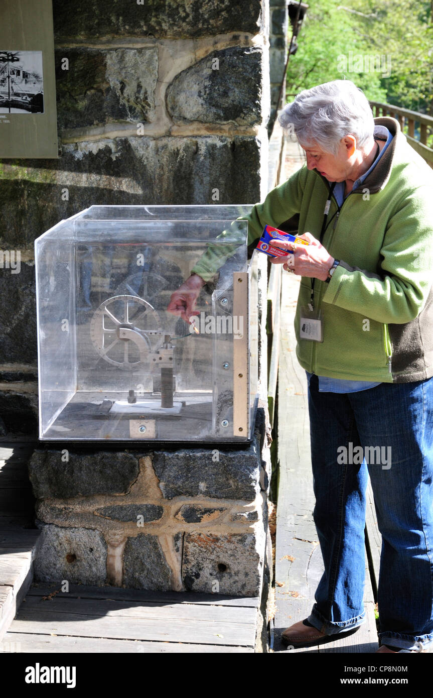 A museum guide lights the charge in the explosives tester at the Hagley museum - Stock Image