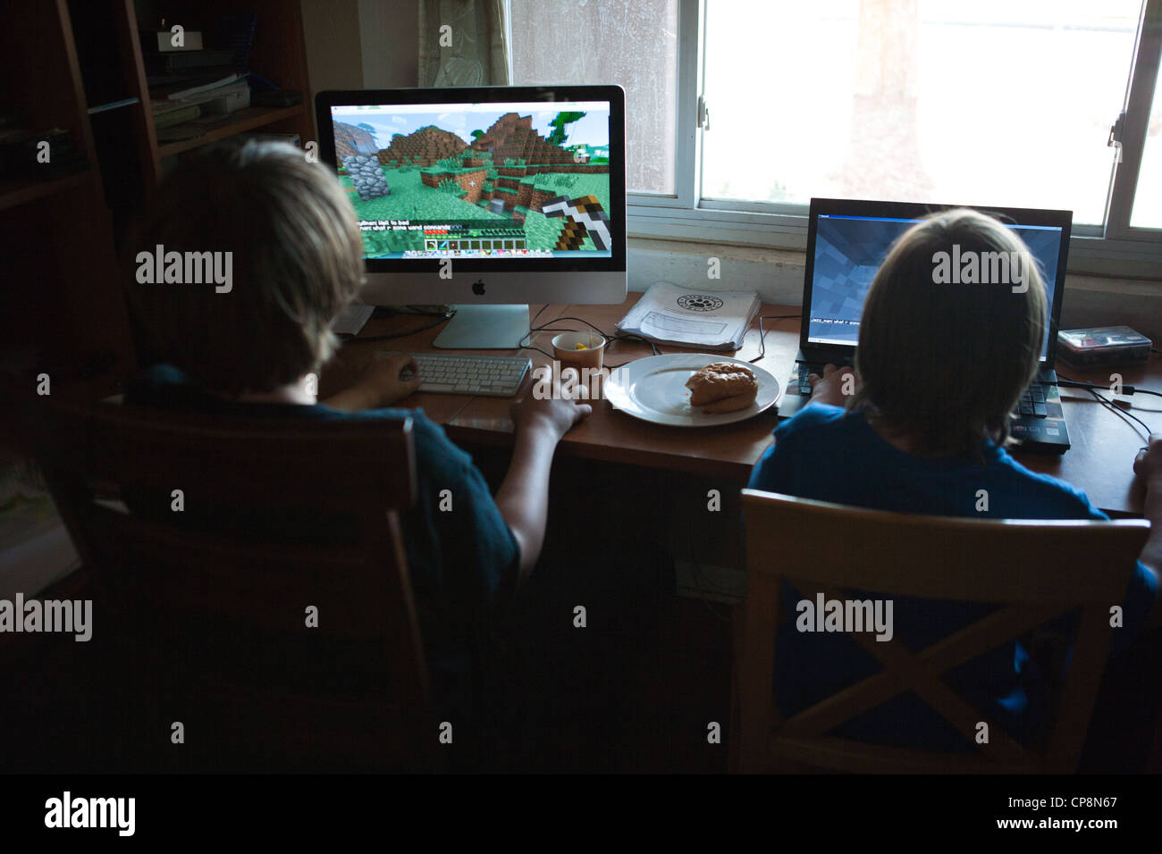 Two boys playing the video game Minecraft at home on computers. - Stock Image
