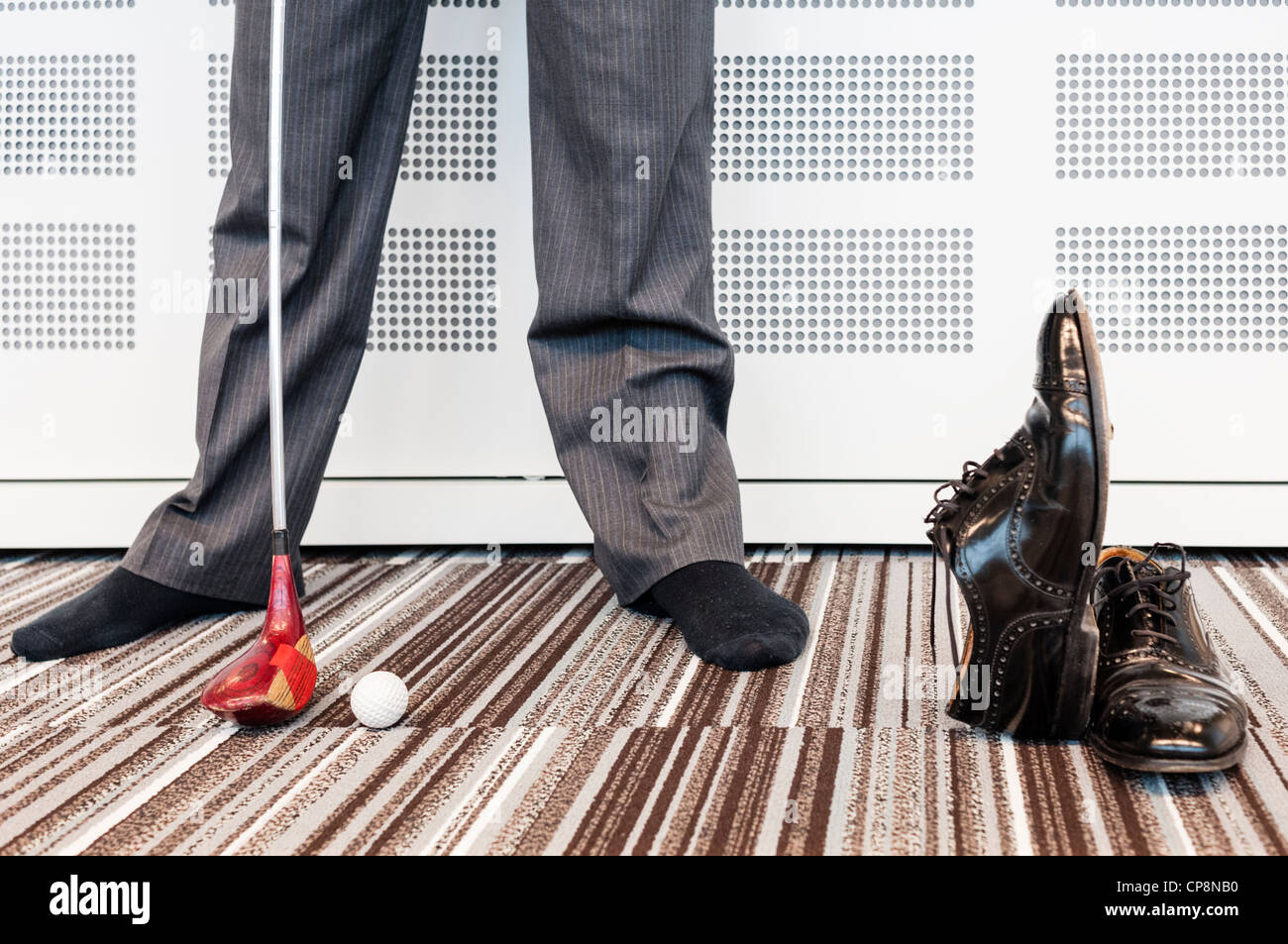 Businessman playing golf in office, low section - model released - Stock Image