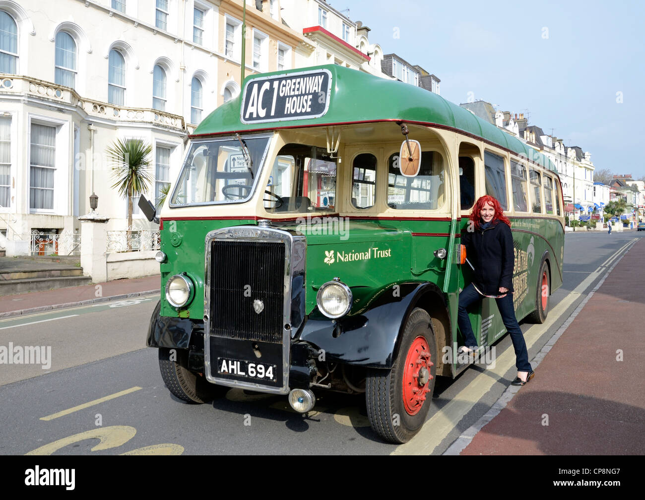 a tourist posing for a photograph before boarding the Agatha Christie tour bus at Torquay in Devon, UK - Stock Image