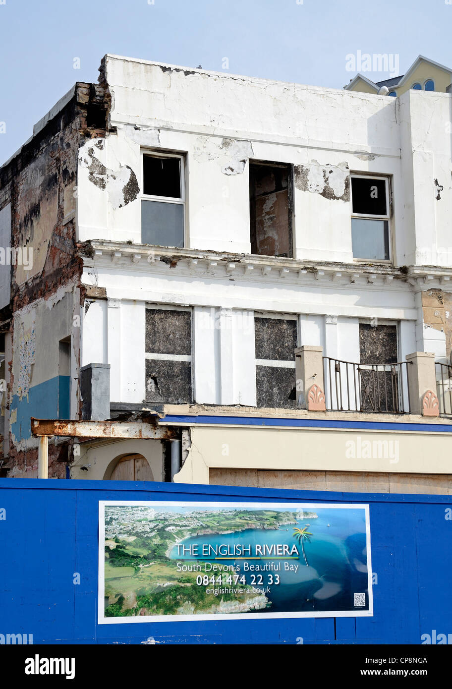 A run down hotel behind a billboard advertising the english riviera at torquay in devon, UK - Stock Image