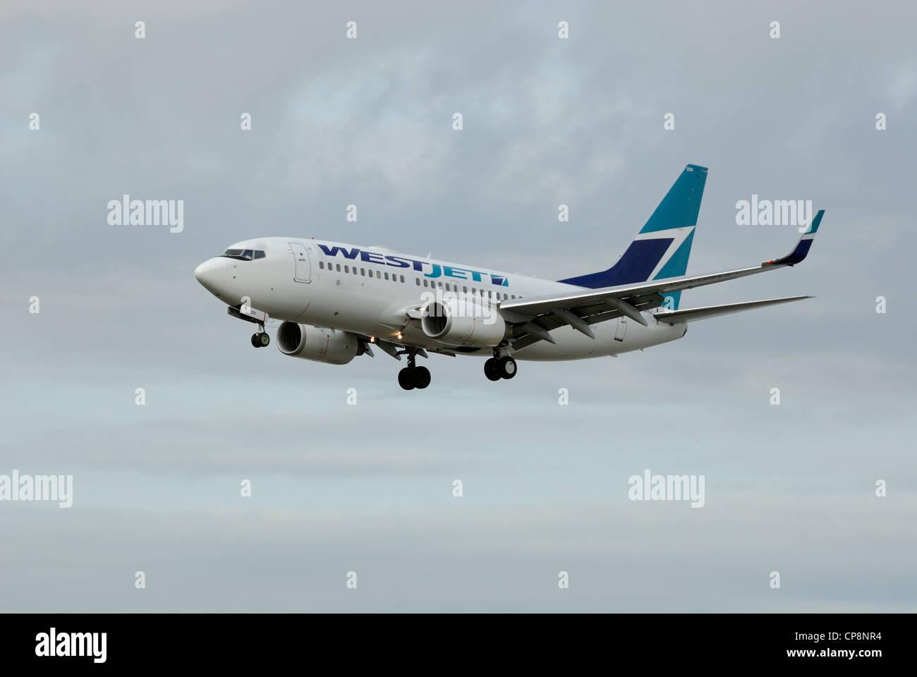 Westjet C-GYWJ Boeing 737-7CT on final approach. - Stock Image