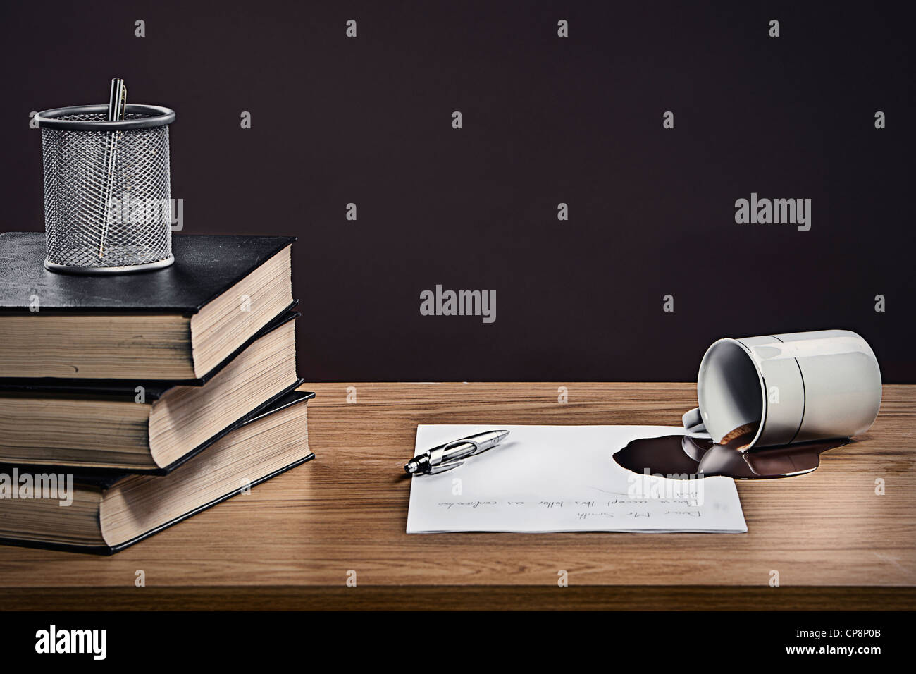 Coffee spilled over letter on desk - Stock Image