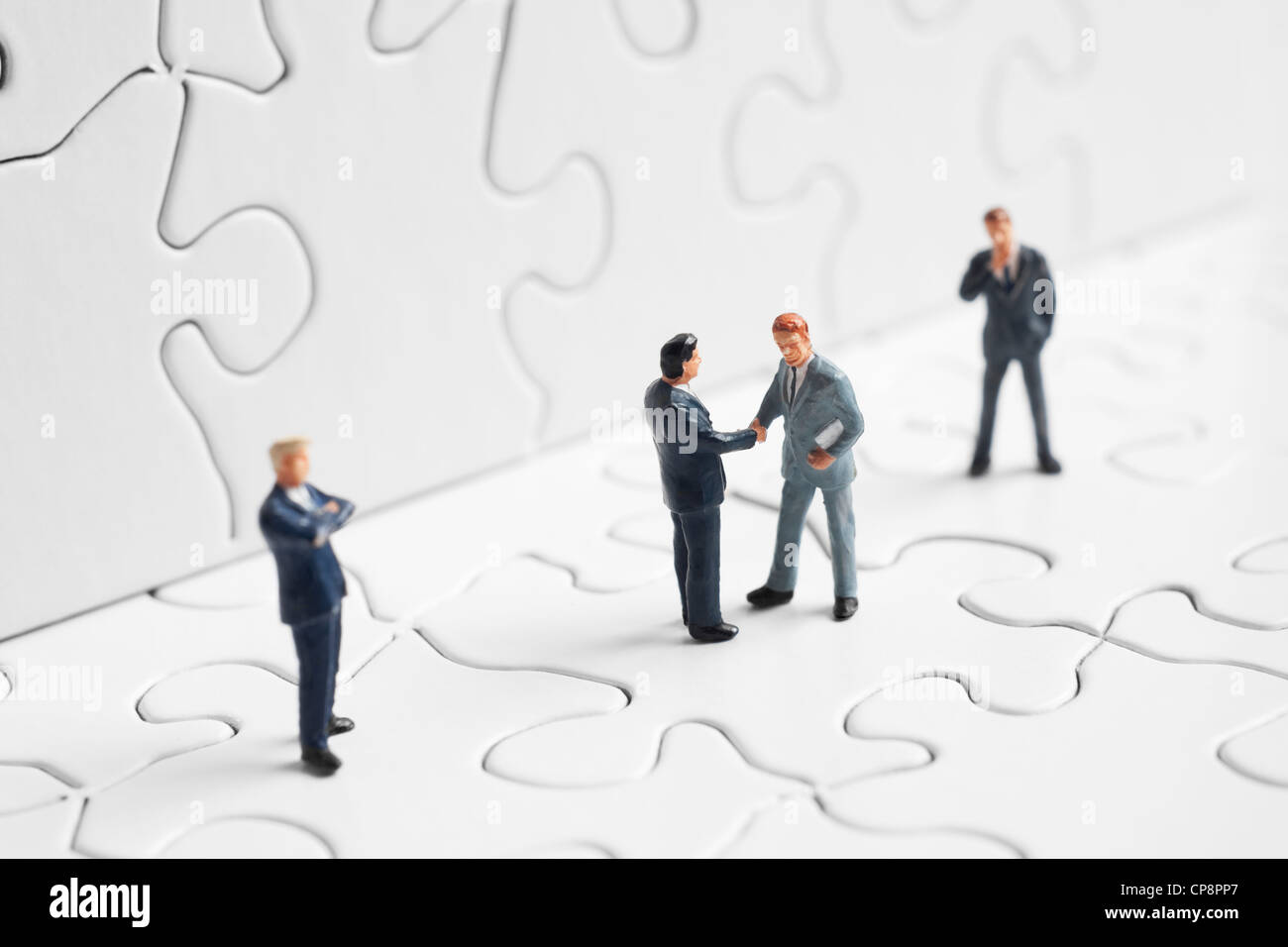 Business figures shaking hands on a puzzle - Stock Image