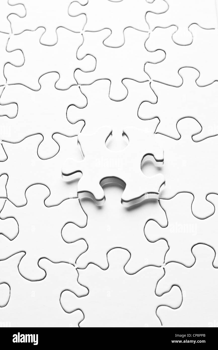 White jigsaw puzzle with one piece floating above - Stock Image