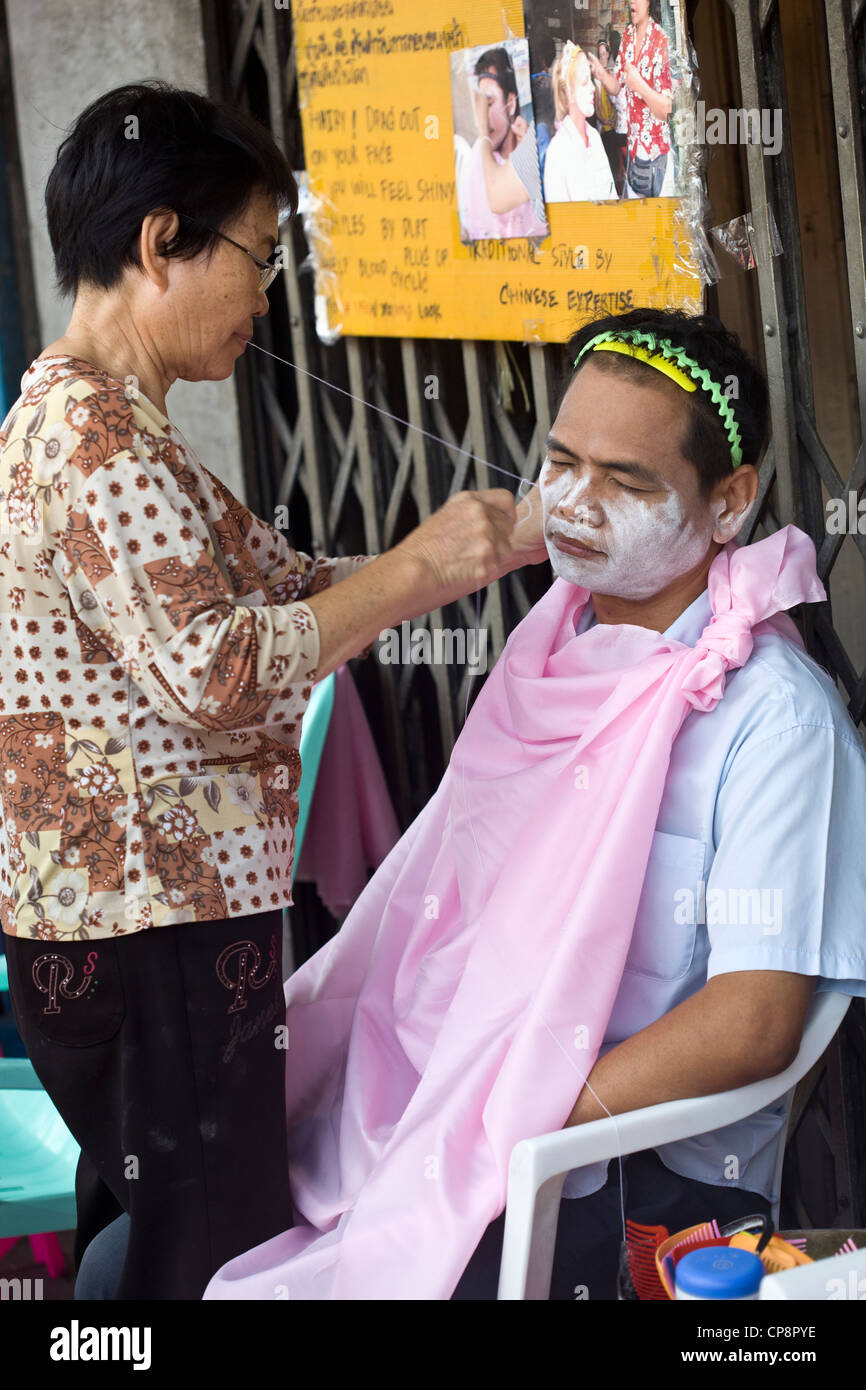Man receiving chinese or asian face cleaning technique on the street - Stock Image