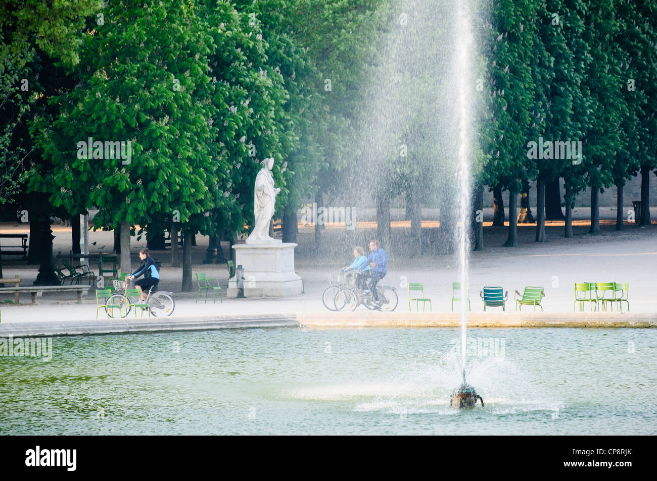 Family riding rental bicycles in the early morning, Jardin des Tuileries, Paris, France - Stock Image