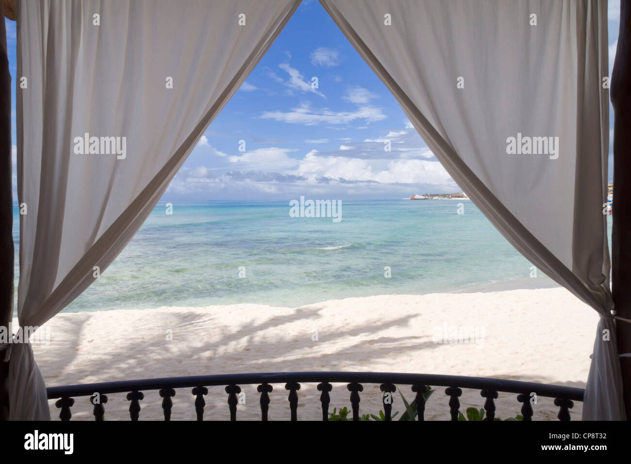 A framed view of the beach and tropical ocean - Stock Image