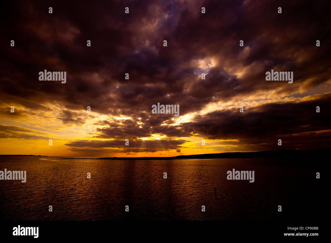 The sun setting across the Loughor Estuary, Swansea. Stock Photo