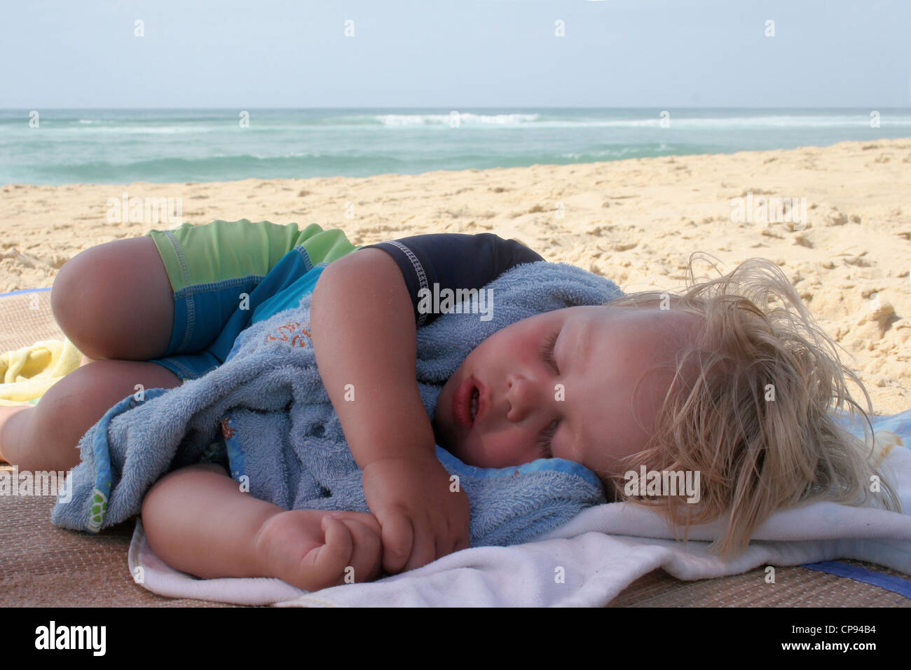 Little boy takes a nap on the beach during the summer holiday - Stock Image