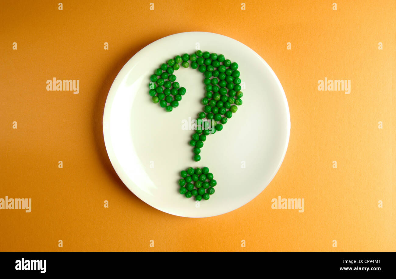 Peas arranged on  plate in a question mark - Stock Image