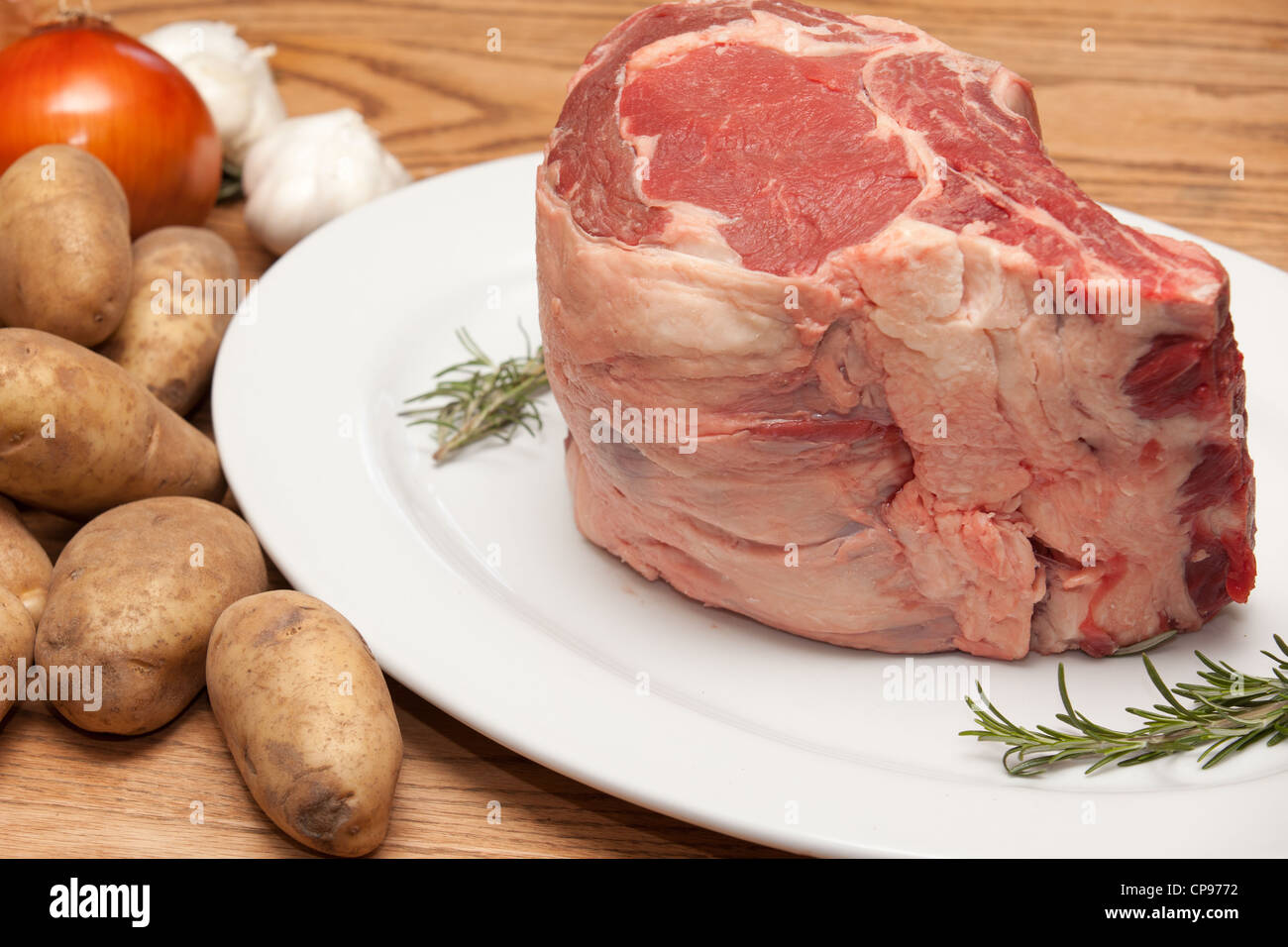 Horizontal view of a large uncooked prime rib roast along with garnishes of herbs, garlic and potatoes. Stock Photo