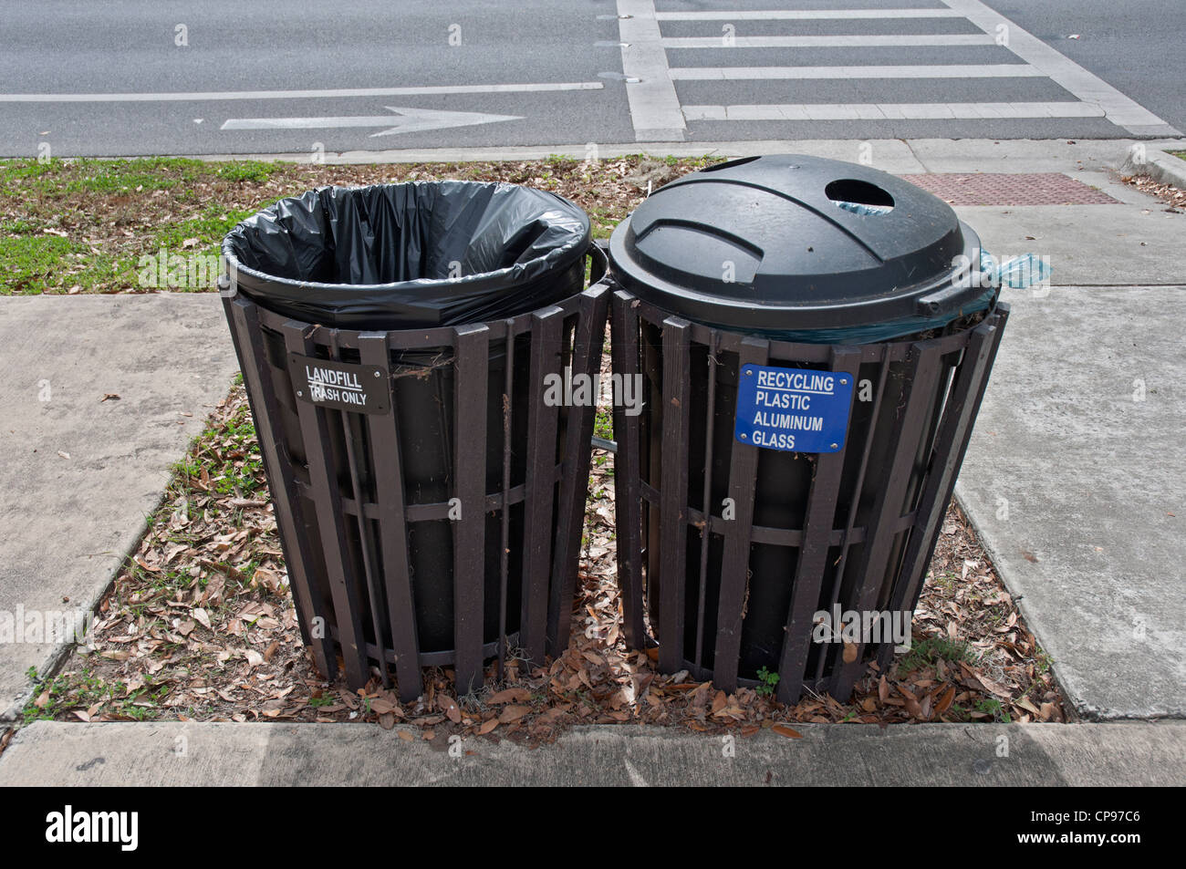 University of Florida campus Gainesville designated trash and landfill recycling bins near crosswalk. - Stock Image