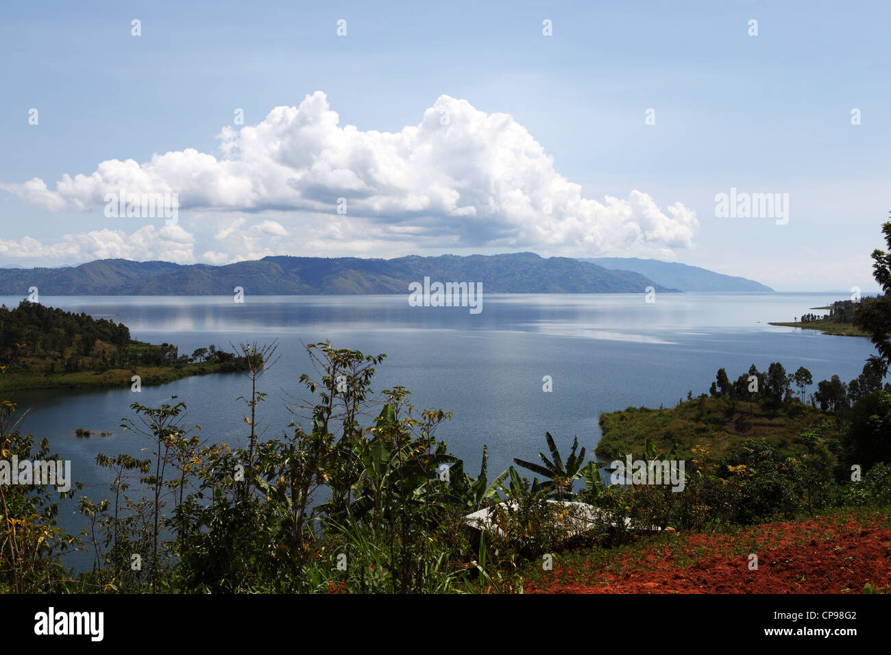 A long white cloud hands over the placid surface of Lake Kivu in Rwanda. - Stock Image