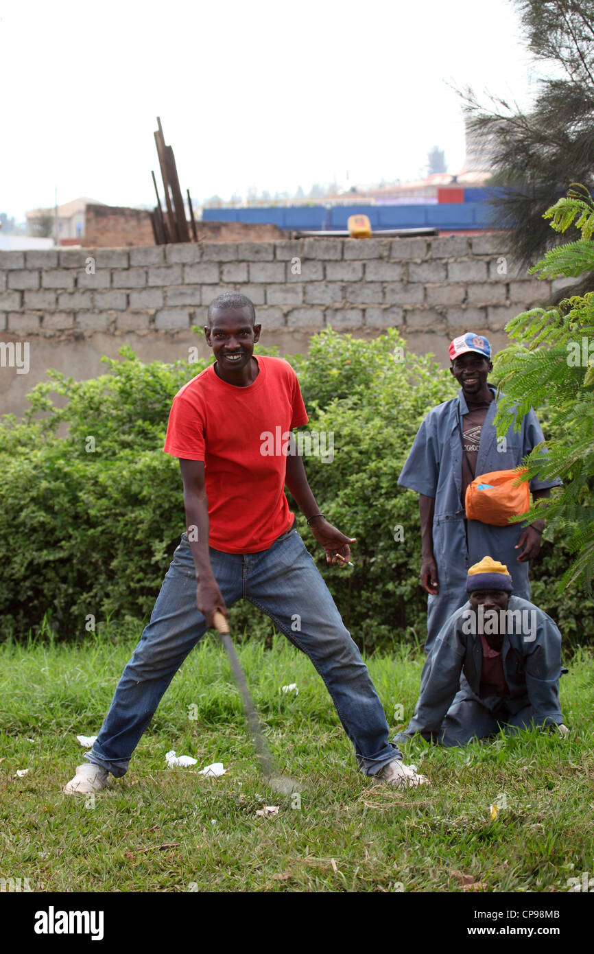 Rwandese men participate in the national clean-up day, Umuganda, in Kigali, Rwanda. - Stock Image