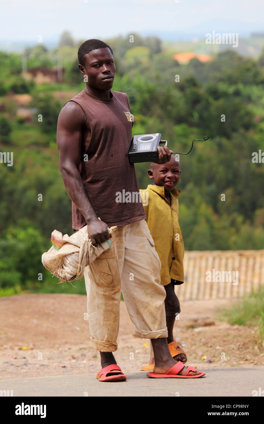 A young man holds a radio on a rural street in the Southern Province of Rwanda. - Stock Image