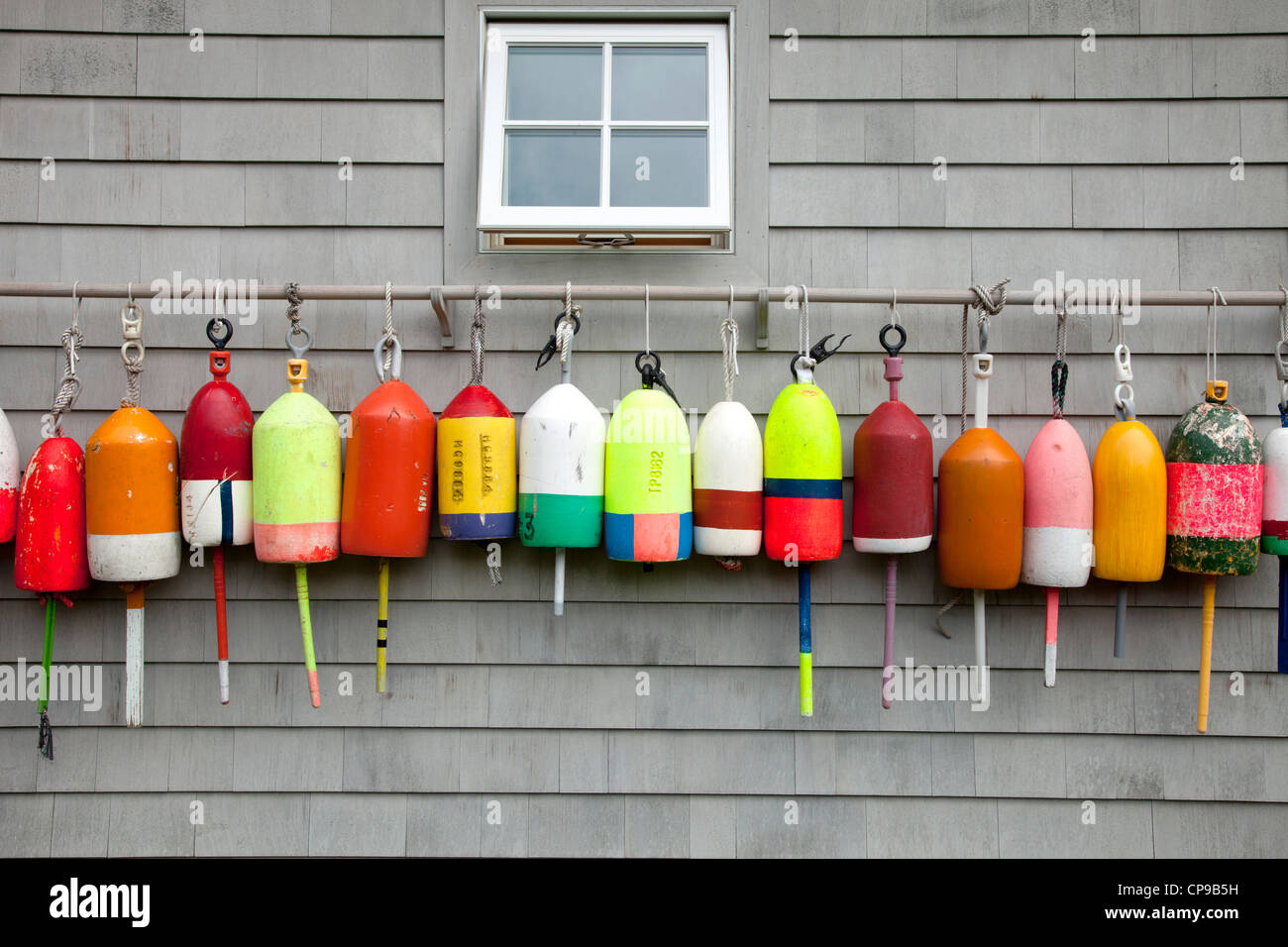 Row of Buoys Hanging on Side of Building, Southampton, New York, USA - Stock Image