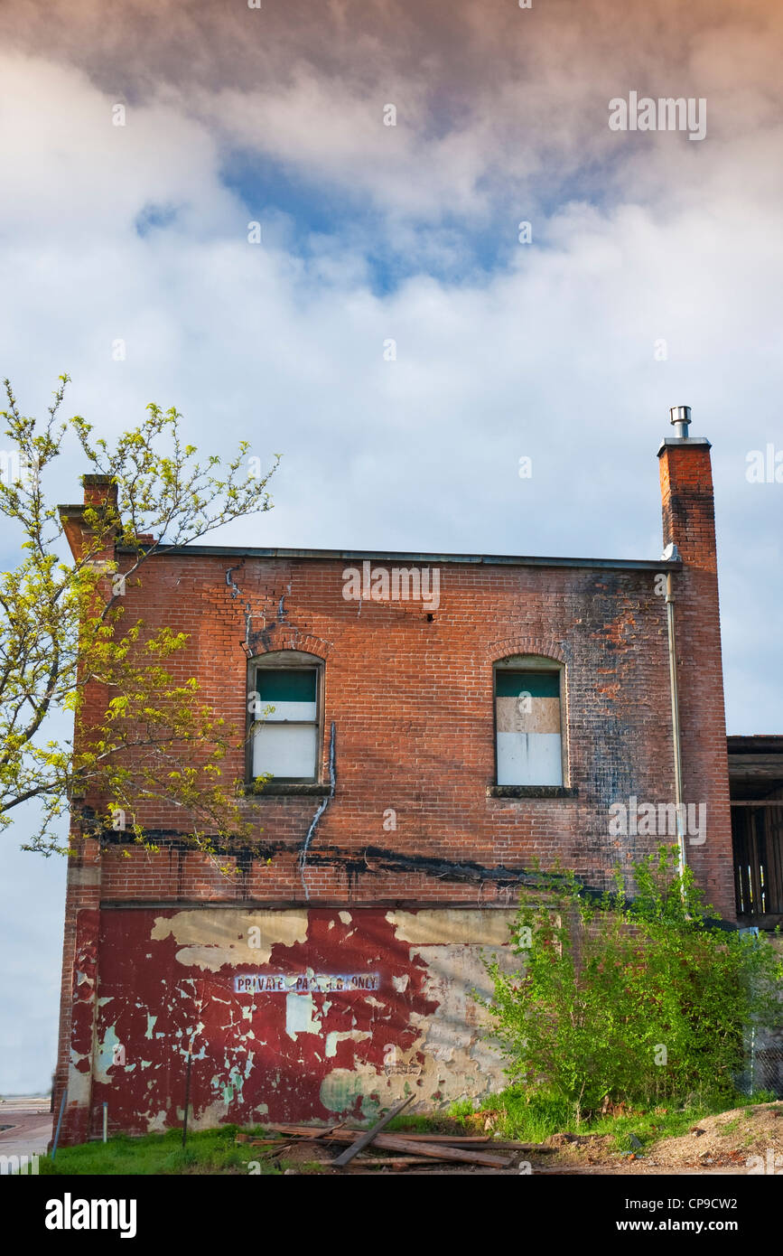Abandon building and what is left of a Private Parking lot - Stock Image
