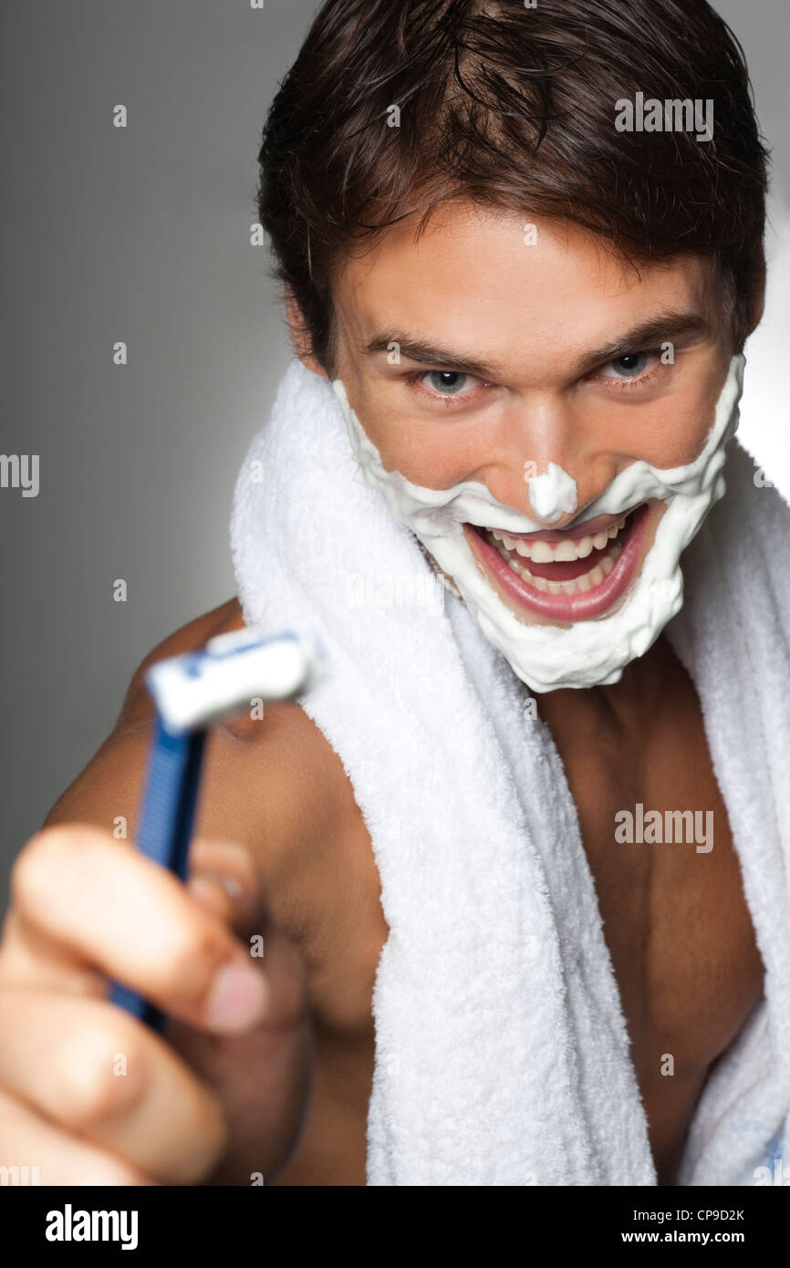 Portrait of healthy looking young caucasian man laughing with shaving cream on face, towel around neck and holding - Stock Image