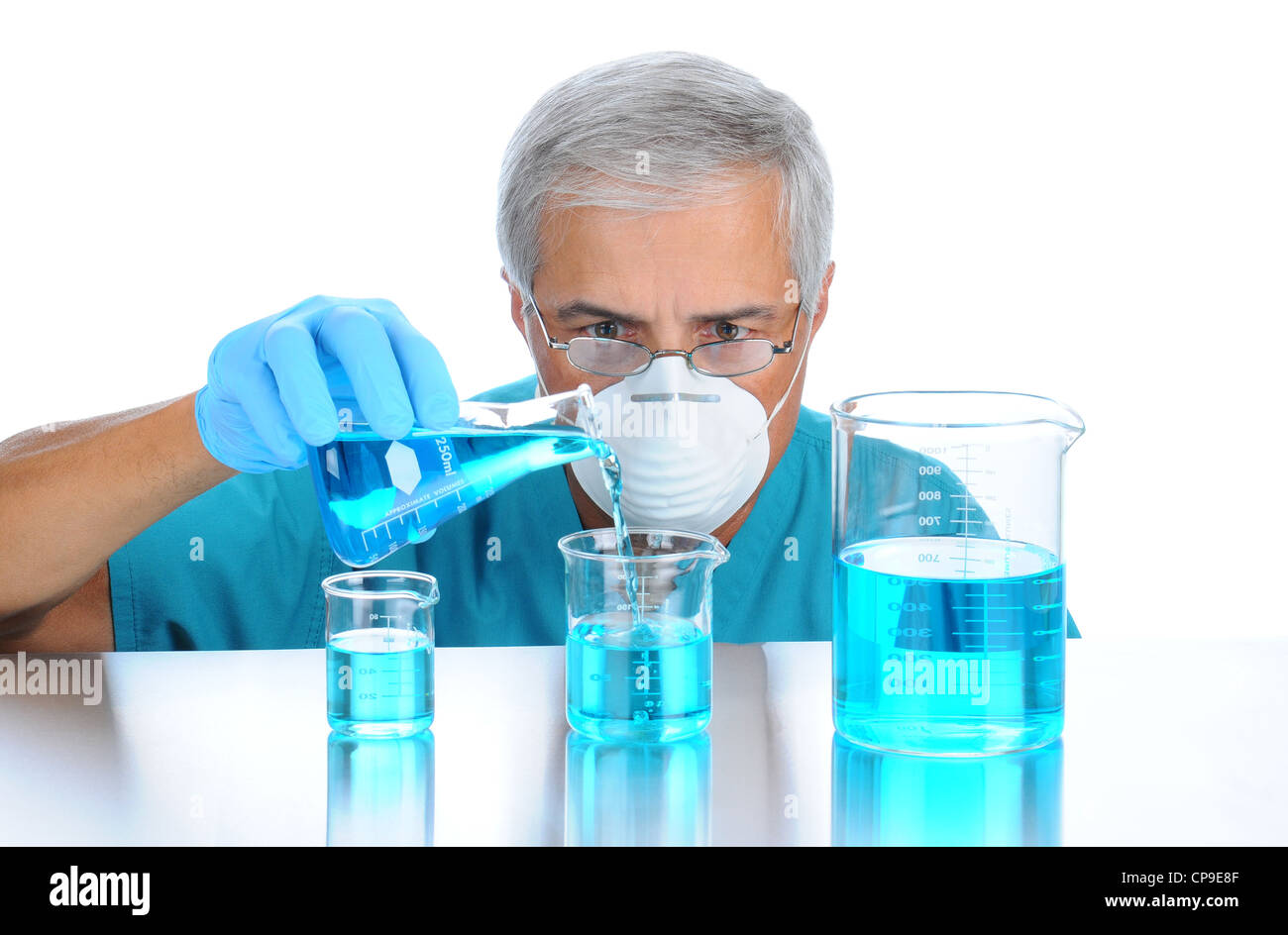 Scientist pouring measuring liquids in assorted beakers. Horizontal format over white background. - Stock Image