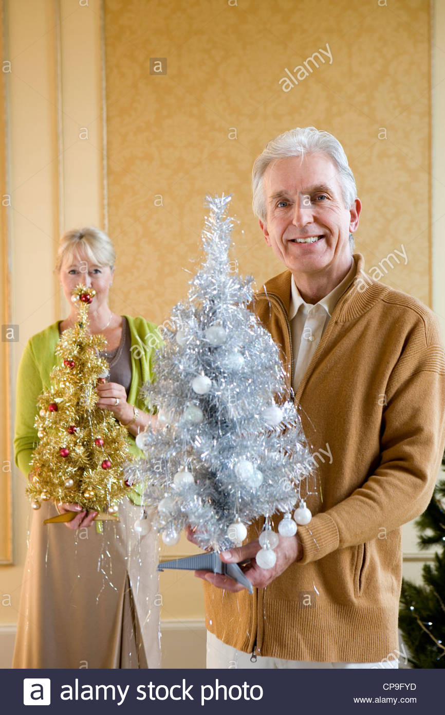 Senior couple with ornamental Christmas trees, smiling, portrait, close-up of man - Stock Image