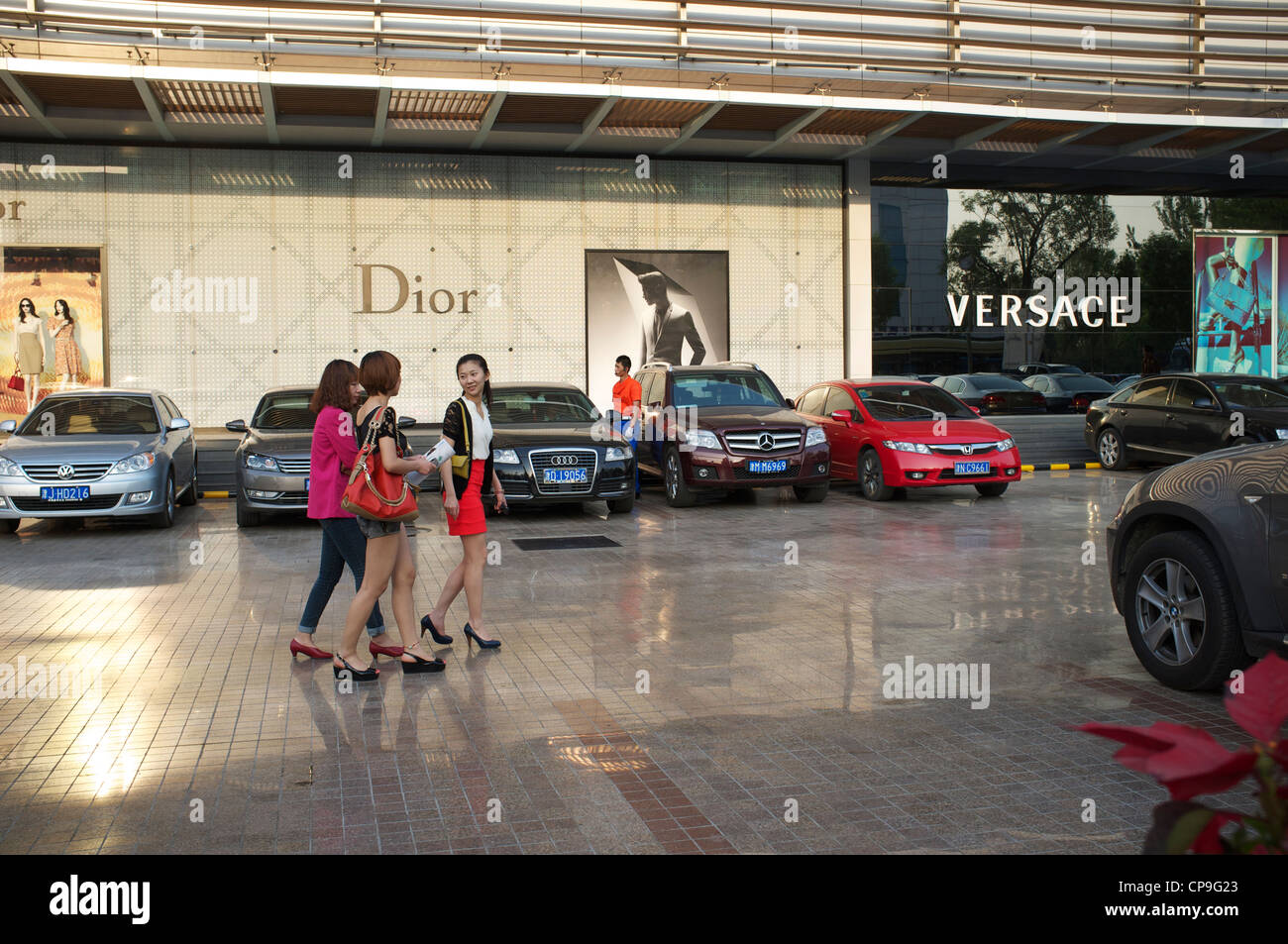 Chinese ladies walk into Friendship Department Store, the first high-end luxury department store in Tianjin, China. - Stock Image